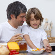 Stock Photo: Portrait of father and son having breakfast together