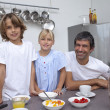Smiling family preparing breakfast — Stock Photo