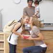 Mother giving her daughter school lunch and kiss — Stock Photo #10317437