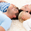 Happy family lying on the floor together — Stock Photo #10317523