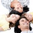 Smiling family lying on the floor together — Stock Photo