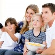 Stock Photo: Smiling family watching a film at television