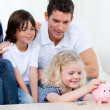 Stock Photo: Positive family using a piggy bank