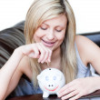 Radiant woman using a piggybank — Stock Photo