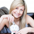 Foto Stock: Delighted womusing piggybank