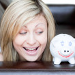 Happy woman using a piggybank — Stock Photo