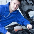 Smiling man repairing a car - Stock Photo