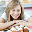 Foto de Stock  : Cheerful woman looking at cakes in the kitchen