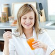 Stock Photo: Cute womhaving breakfast in kitchen