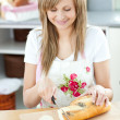Delighted woman cutting bread in the kitchen — Stockfoto