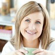 Stock Photo: Happy womholding cup of coffee in kitchen