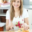 Stock Photo: Smiling womcuting bread in kitchen