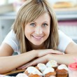 Delighted woman eating cakes in the kitchen — Stock Photo #10318783