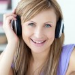 Delighted woman using headphone in the kitchen — Stock Photo