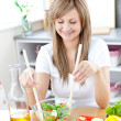 Stock Photo: Radiant wompreparing salad in kitchen