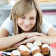 Delighted woman looking at cakes in the kitchen — Stock Photo #10318852