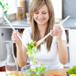 Smiling woman preparing a salad in the kitchen — Stock Photo