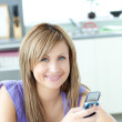 Teen woman sending a text in the kitchen — Stock Photo