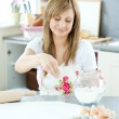 Portrait of a young woman preparing a cake in the kitchen — Stock Photo