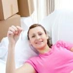 alegre mujer descansando en un sofá con cajas — Foto de Stock