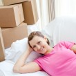 Happy woman relaxing on a sofa with boxes — Stock Photo