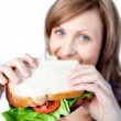 Smiling woman holding a sandwich — Stock Photo