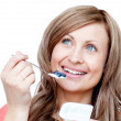 Happy woman eating a yogurt — Stock Photo