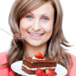 Cheerful woman eating a cake — Stock Photo