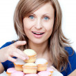 Pretty woman eating a cake - Stock Photo