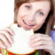 Happy woman eating a sandwich — Stock Photo
