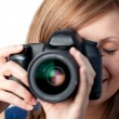 Beautiful woman using a camera - Stok fotoğraf