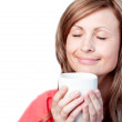 Delighted woman drinking a cup of coffee — Stock Photo