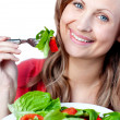 Royalty-Free Stock Photo: Smiling woman is eating a salad
