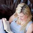 Stock Photo: Joyful womreading book on sofa