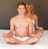 Smiling couple doing exercises on bed — Stock Photo