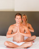 Couple doing exercises on bed — Stock Photo
