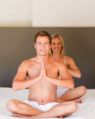 Young couple doing yoga moves on bed — Stock Photo