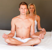 Couple doing meditating on bed — Stock Photo