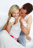 Couple in bed drinking coffee with affection — Stock Photo