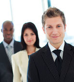 Friendly businessman in front of his team — Stock Photo
