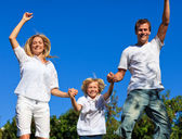 Young family jumping in the air against thr blue sky — Stock Photo