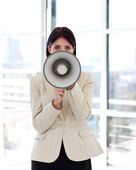 Businesswoman shouting through megaphone to the camera — Stock Photo