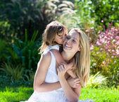 маленькая девочка, целуя ее мать — Стоковое фото