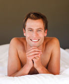 Young man relaxing in bed smiling at the camera — Stock Photo