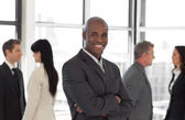 Happy business leaderlooking at camera in front of team — Stock Photo