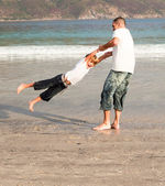 Father and son playing on a beach — Stock Photo