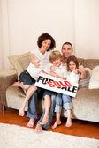 Happy family sitting on a sofa — Stock Photo