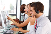 Attractive businessman working in a call center — Stock Photo