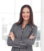 Smiling young businesswoman with folded arms — Stock Photo