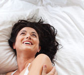 Lovely woman lying on a bed — Stock Photo